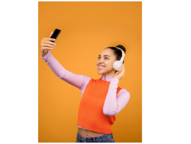 woman with headphones and looking at phone; orange background