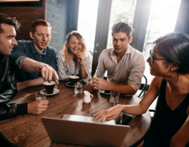 Group of young professionals discussing client on laptop